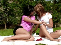 Lesbian girlfriends caress each other and play with twats on a picnic